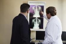 doctor-pointing-x-ray-result-beside-man-wearing-black-suit-2182972.jpg