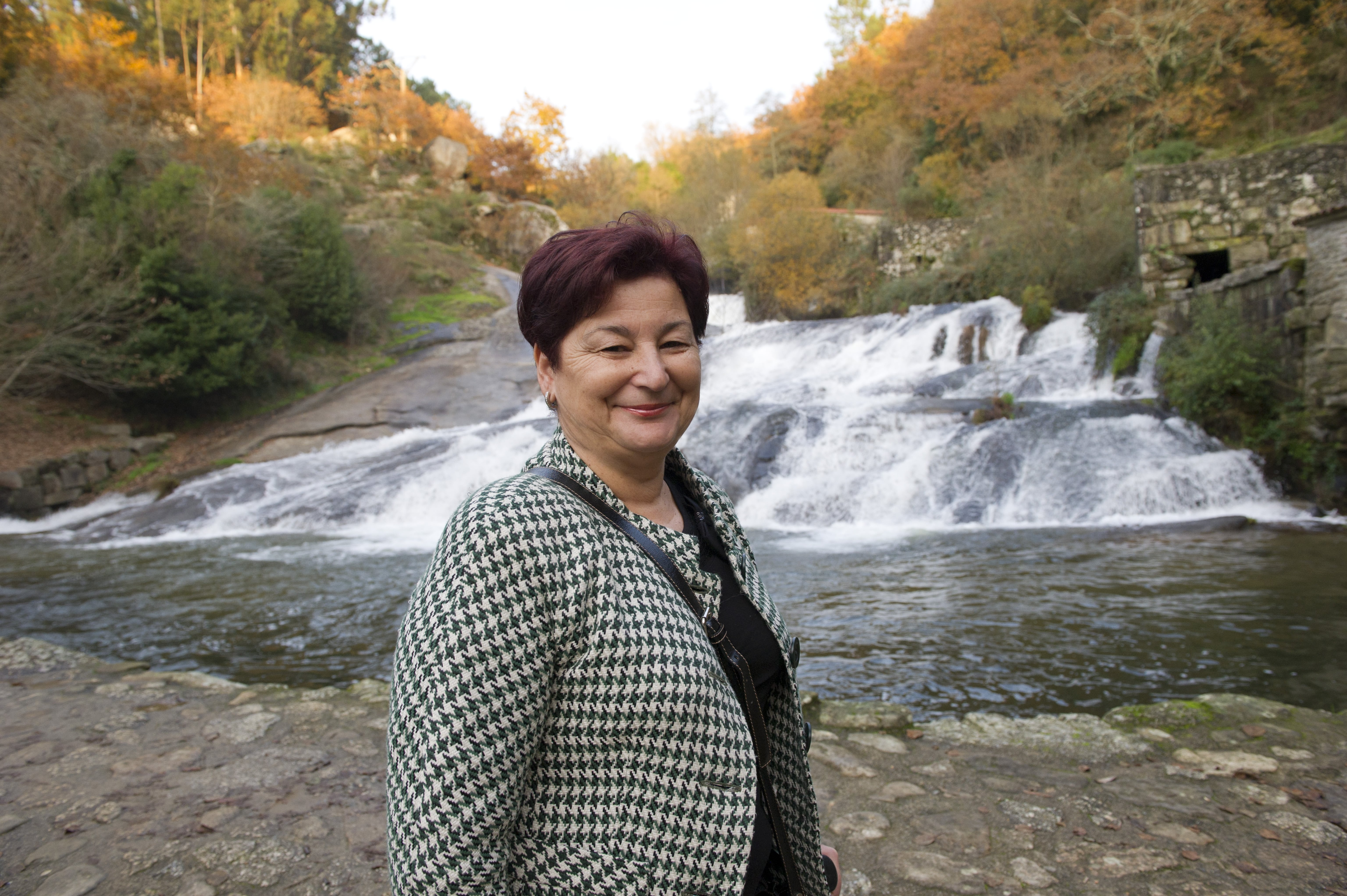 A smiling woman standing in front of a waterfall.